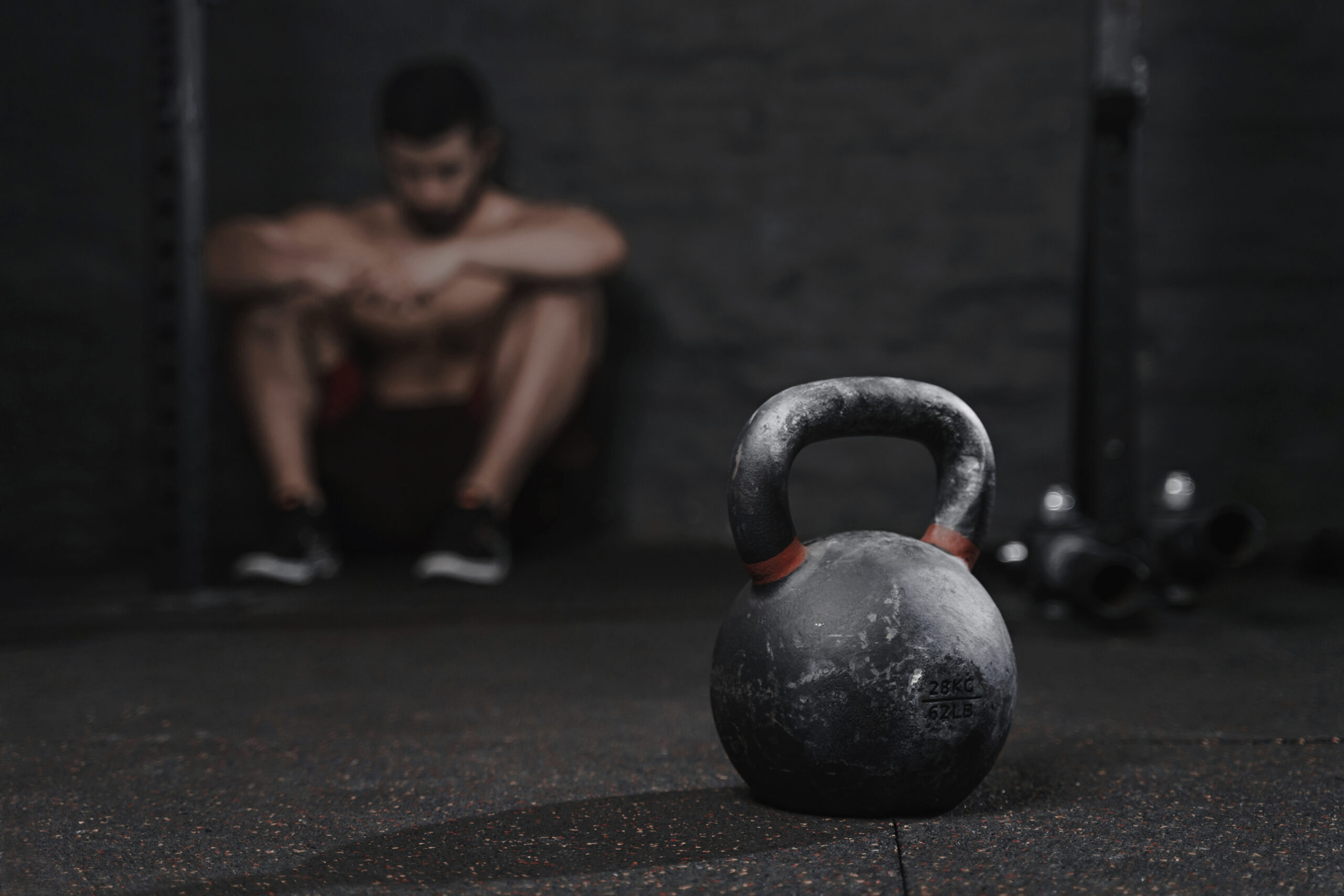 Sporty man sitting at the gym suffering breakdown to overcome. Demotivation sport concept. Stress and fatigue in sport. Crossfit kettlebell training.