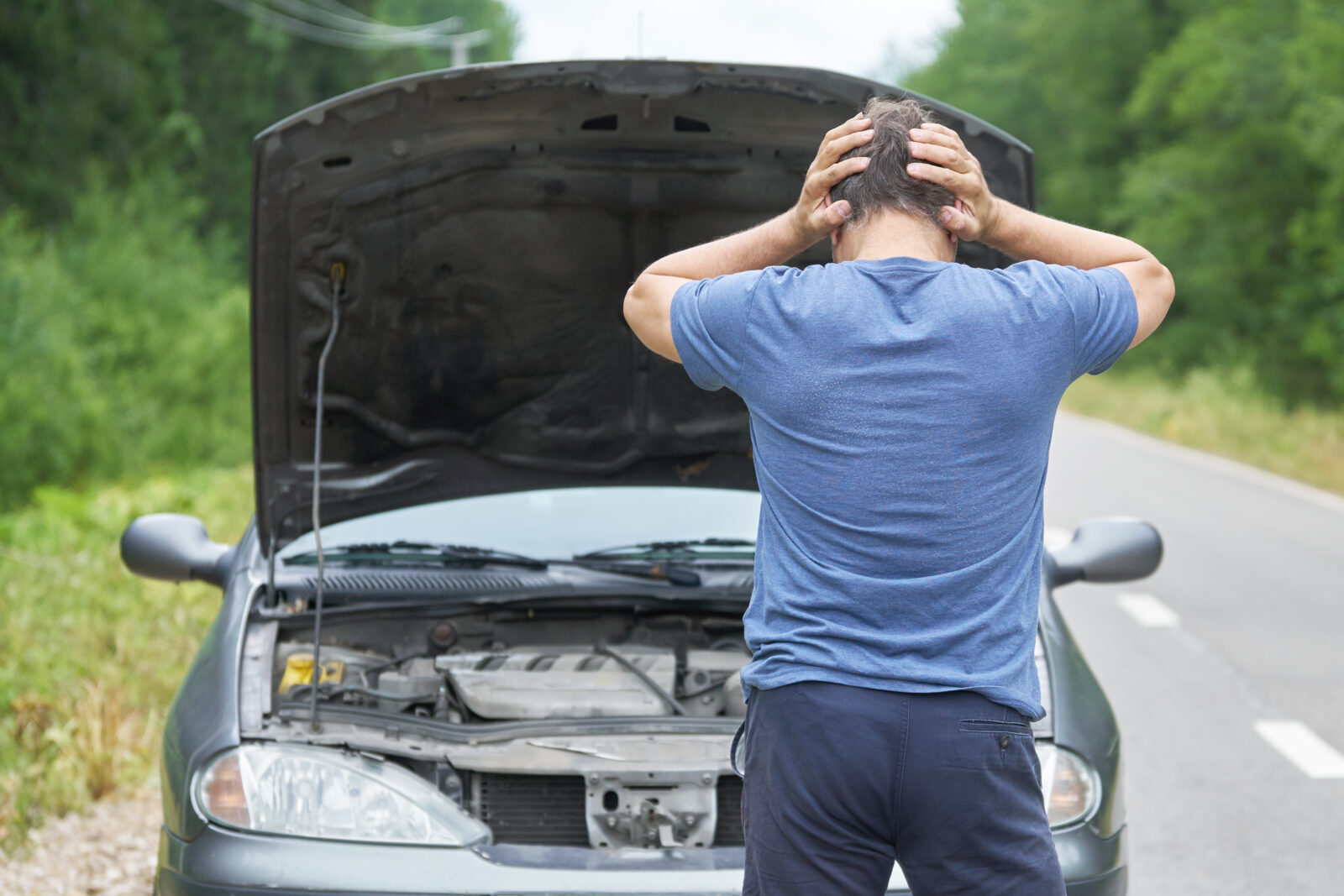 Middle-aged man stands with his hands on the head near his broken car